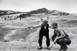 ITALY. Near Troina. August 4-5, 1943. Sicilian peasant telling an American officer which way the Germans had gone. Didascalia © Robert Capa © International Center of Photography / Magnum Photos
